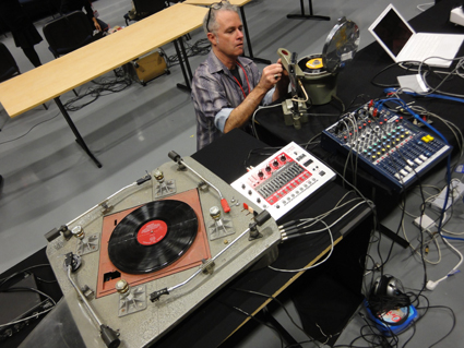 Ian Andrews preparing a medical centrifuge modified to play vinyl records at extremely high speeds, with four-arm turntable constructed by John Jacobs,  photo Alessio Cavallaro