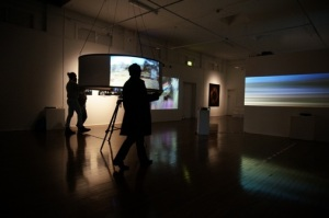 Foreground: Juxtaposition, Volker Kuchelmeister, 2010, Interactive video installation, custom interactive panoramic projection system, 3D panorama montage; Background: A dromological vision machine, 2013, Interactive video installation, time variable, courtesy the artist